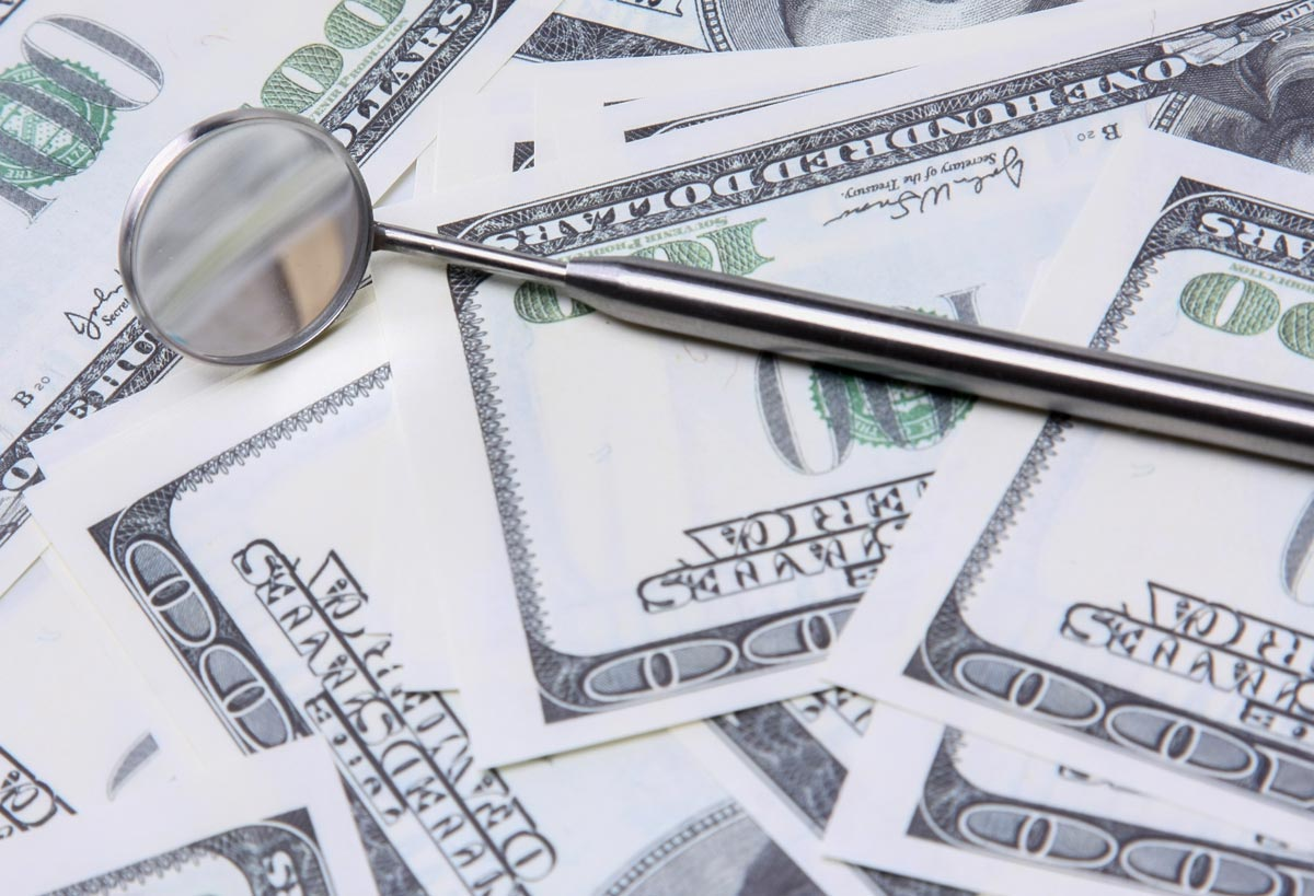 A stack of bills and a dental instrument represent the costs of dental care.